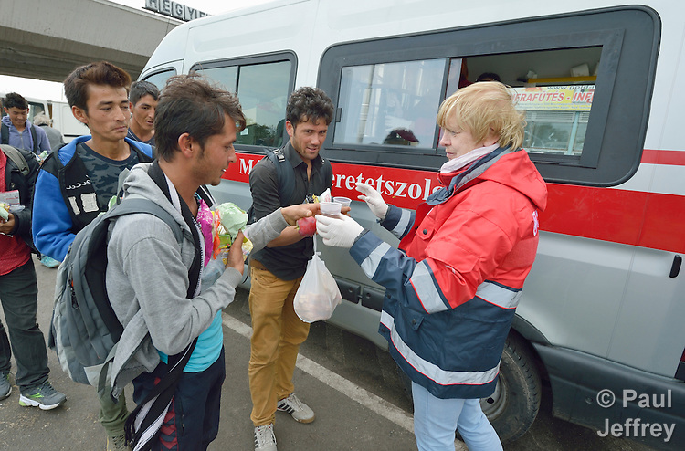 Hungarian volunteers with Malteser International, a Catholic organization, give coffee to migrants and refugees as they pass through the Hungarian town of Hegyeshalom and prepare to cross the border into Austria. Hundreds of thousands of refugees and migrants flowed through Hungary in 2015, on their way to western Europe from Syria, Iraq and other countries. Malteser International is the relief agency of the Sovereign Order of Malta.