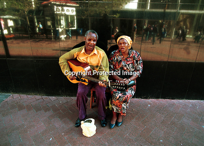 dimubus00024 Buskers. Street musicians playing in Adderly street, a main shopping street in the center of Cape Town, South Africa; homeless couple busking; man playing a guitar; begging..©Per-Anders Pettersson/iAfrika Photos