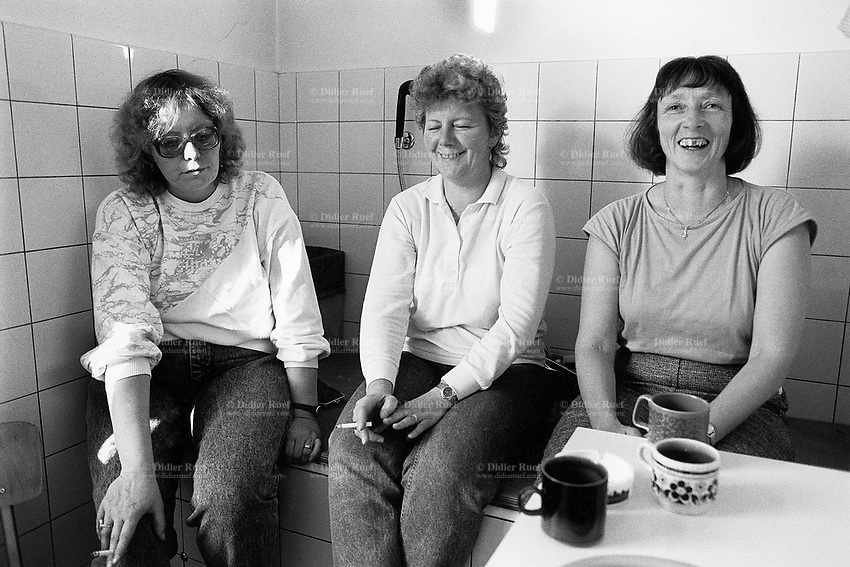 Switzerland. Canton Bern. Frutigen. Three blue collar workers. all women, take a break from work. They rest sitting on a wooden board covering a bathtub. They smoke a cigarette and drink coffee. Two women are happy, one is sad. © 1988 Didier Ruef