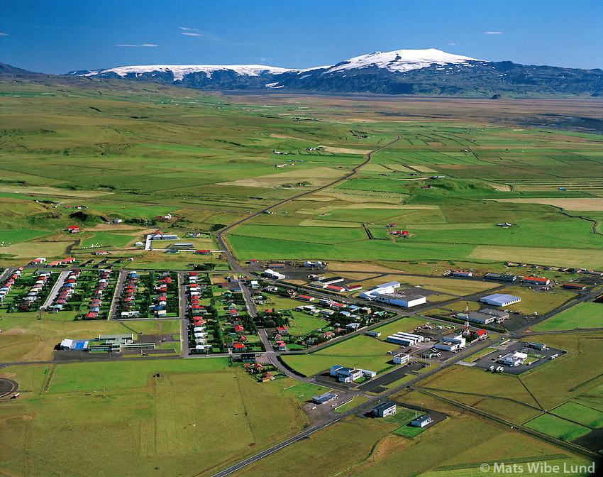 Hvolsvöllur, Fljótshlíð, Mýrdalsjökull og Eyjafjallajökull.Hvolsvollur town at main road no. l. In the background Fljotshlid agricultural district and the glaciers Myrdalsjokull left and Eyjafjallajokull right..Between the two glaciers is Thorsmork national park