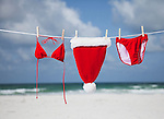 USA, Florida, St. Pete Beach, Santa hat and bikini hanging on clothesline on beach