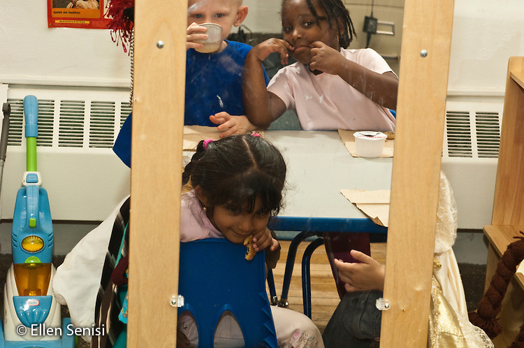 MR / Schenectady, New York. Fulton Early Childhood Education Center (urban public school early childhood education center). Pre-K classroom. Students make faces while looking at themselves in the mirror of the house corner at snack time. ID: AI-gPd. ©Ellen B. Senisi
