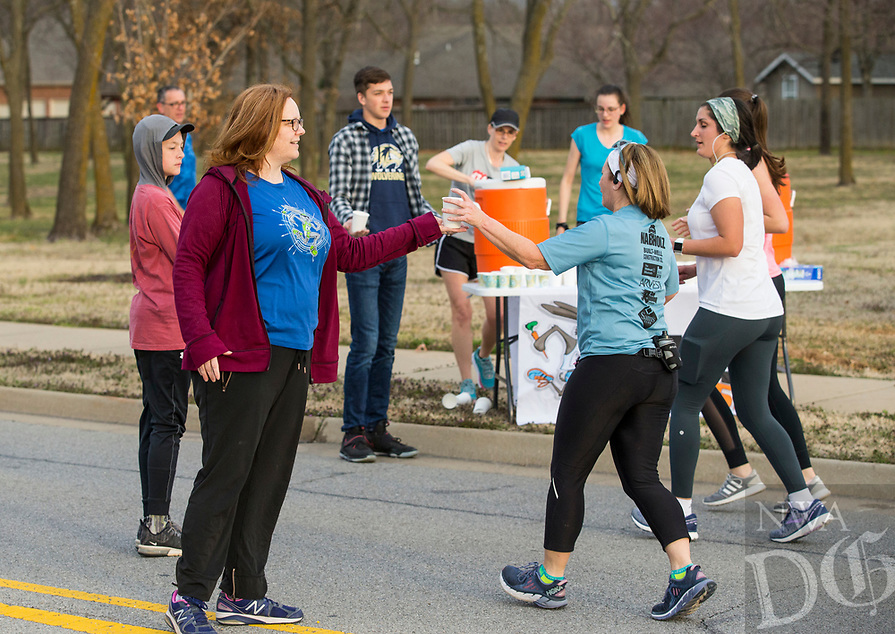 NWA Democrat-Gazette/BEN GOFF @NWABENGOFF<br /> Laurie Glenn (left) of Cave Springs supports runners at an aid station Saturday, March 23, 2019, during a half marathon training run at Memorial Park in Bentonville. Volunteers from Flagstone Church of Christ in Bentonville set up the aid station as participants in the Run Bentonville Half Marathon training program took their final group run before the March 30 half marathon. The training program, run by Mike Rush of Rush Running Company, has been preparing runners with clinics and group runs since December. Flagstone Church of Christ was also promoting their Jack Rabbit 5K, set for April 13, which works with Rush Running Company to donate shoes to local families in need.