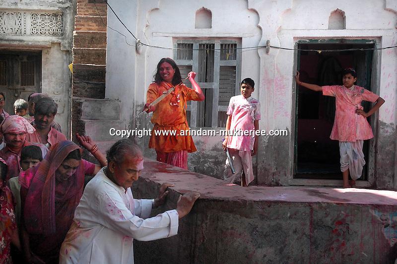 A local boy sprays water by a colour spray gun at Nandgaon on a lady the next day of Barsana Holi.
