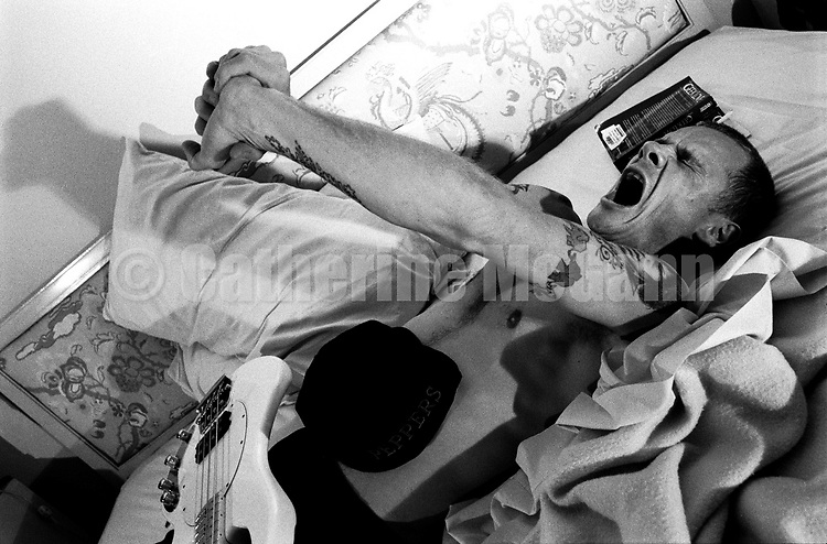 NEW YORK - AUGUST 1992:  Musician Flea of the Red Hot Chili Peppers stretches and yawns on his bed during a  photo shoot in his hotel room in August 1992 in New York City, New York. (Photo by Catherine McGann).Copyright 2010 Catherine McGann