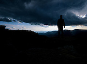 The silhouette of hiker during a storm on Bondcliff Mountain in the Pemigewasset Wilderness of the White Mountains, New Hampshire USA.