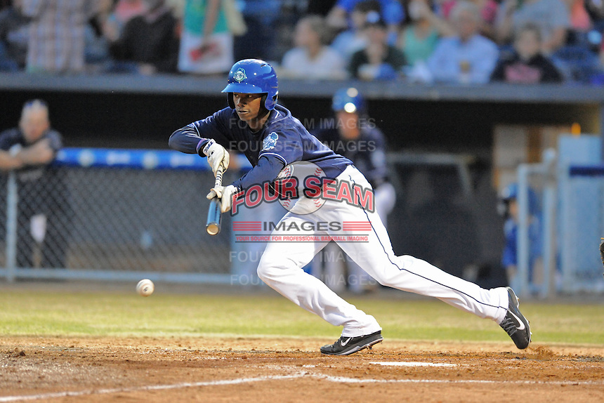 Asheville Tourists left fielder Raimel Tapia #15 lays down a drag bunt during opening night game against the Delmarva Shorebirds at McCormick Field on April 3, 2014 in Asheville, North Carolina. The Tourists defeated the Shorebirds 8-3. (Tony Farlow/Four Seam Images)