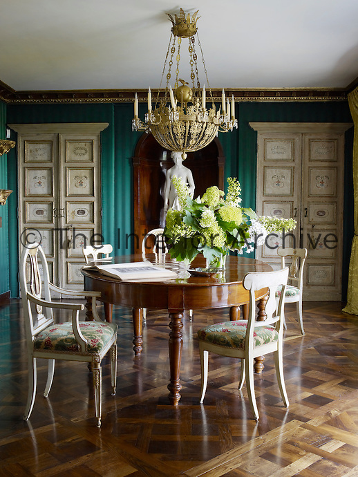 An ante-room adjoining the library has walls covered in a turquoise striped fabric contrasting with hand-painted Florentine cupboard doors