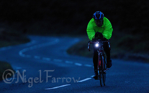 10 JUN 2011 - BRANSGORE, GBR - As the light fails Chris Ette  continues making his way around the bike course during the Triple Enduroman race at the Enduroman Ultra Triathlon Championships with lights on his bike and wearing a reflective jacket .(PHOTO (C) NIGEL FARROW)