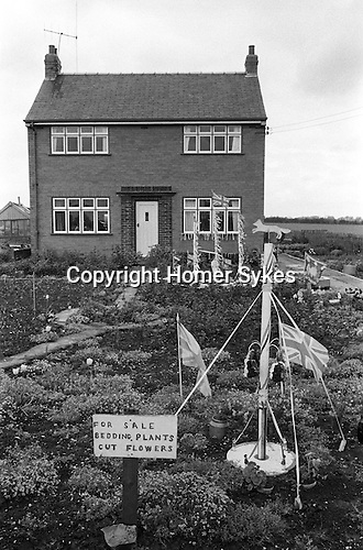 Barwick in Elmet  Spring bank holiday Tuesday Yorkshire England 1972. A local gardener shows off  replica Maypoles in his front garden.
