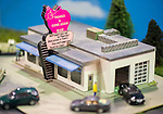 "Hicksville, New York, USA. February 22, 2015. A scene with an old fashioned Car Wash with a retro pink elephant rooftop sign with elephant puns in the message, and model classic cars is recreated at the Model Train Exhibit hosted by Trainville Hobby Depot at the Broadway Mall, including an N Scale layout, the Long Island HOTrack train club HO scale model train portable modular layout, and others. Donations were accepted at exhibit to support the Nassau County Empire State Games for the Physically Challenged. Pink elephant Sign has play on words: ""We'll wash your car for Peanuts... Plus we'll clean your Trunk for Free."""