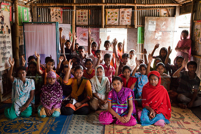 Members of a children's group raise their hands to count those who have official birth certificates during a monthly meeting of a Children's Group in Bhashantek Basti (Slum) in Zon H, Dhaka, Bangladesh on 23rd September 2011. Official birth certificates is essential in proving that a child is underaged for marriage as many parents lie about their child's age when asked. The Bhashantek Basti Children's Group is run by children for children with the facilitation of PLAN Bangladesh and other partner NGOs. Slum children from ages 8 to 17 run the group within their own communities to protect vulnerable children from child related issues such as child marriage. About 20150 people live in the Bhashantek urban slum, with an average household size of 5 in housing sizes of 8 x 9ft made of bamboo, tin sheets and scrap materials. The average annual income is USD 200. Photo by Suzanne Lee for The Guardian