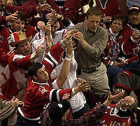Fans grab for a flying hockey puck. First period. Czech Republic vs. Canada, Mens Hockey, Monday afternoon at the E Center, 2002 Olympic Winter Games.; 02.18.2002, 6:01:45 PM<br />