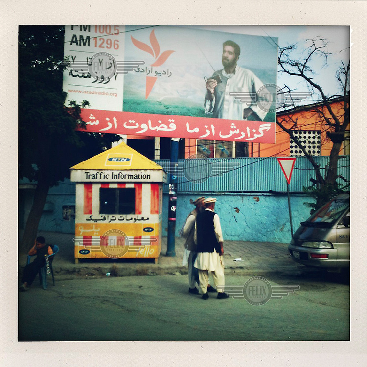 Two men stand together below a billboard advert for Azadi Radio, a station operated by Radio Free Europe/ Radio Liberty and funded by the American Government.