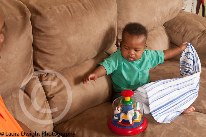 Baby boy 10 months old at home pulling cloth off hidden toy
