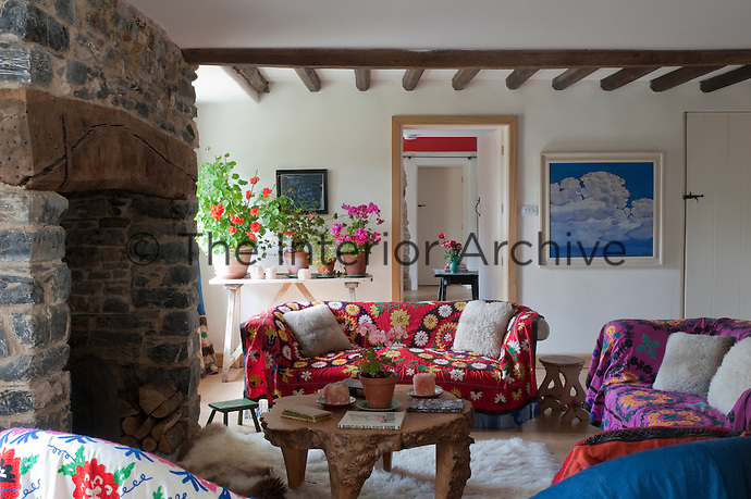 The living room furniture is covered in colourful Afghan throws and a simple table displays a collection of geraniums