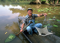 A smiling Cajun man fishing from his boat displays a net of crayfish hge has caught in a bayou. Louisiana.
