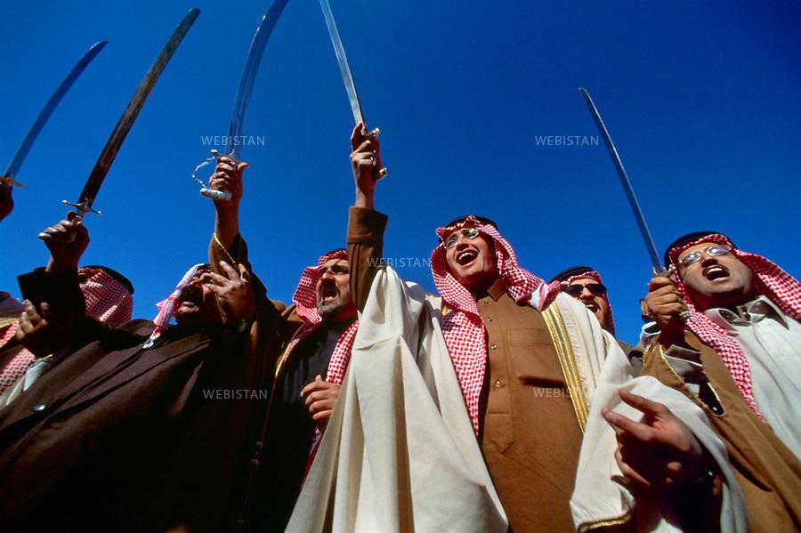 """2003. Saudi Arabia. Om Rogheiba. During an annual meeting of the royal family, Al Saud princes perform the traditional Bedouin sabre dance called """"Arda"""". Arabie saoudite. Om Rogheiba. Lors d'une réunion annuelle de la famille royale, des princes Al Saoud exécutent la danse traditionnelle bédouine du sabre appelée """"Arda""""."""