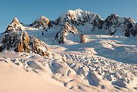 Crevasses and seracs of Explorer Glacier on top of Fox Glacier during setting sun with Mt. Tasman dominating skyline, Westland Tai Poutini National Park, West Coast, UNESCO World Heritage Area, New Zealand, NZ