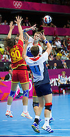 28 JUL 2012 - LONDON, GBR - Kathryn Fudge (GBR) of Great Britain (top right, in white, blue and red) passes to Lyn Byl (GBR) (bottom right) during the women's London 2012 Olympic Games Preliminary round handball match against Montenegro at The Copper Box in the Olympic Park, in Stratford, London, Great Britain .(PHOTO (C) 2012 NIGEL FARROW)