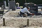 Foto: VidiPhoto<br /> <br /> VALBURG &ndash; Geen stille, maar een actieve zaterdag bij de Hervormde gemeente Valburg-Homoet. Een twintigtal jonge en ouderden vrijwilligers was aanwezig op de jaarlijkse schoonmaakdag van de kleine kerkelijke gemeente om de graven schoon te maken, onkruid te wieden en de struiken en bomen te snoeien. Voor het eerst gebeurde dat op de zogenoemde Stille Zaterdag, de dag tussen Goede Vrijdag en Pasen. Volgens de gemeente een uitgelezen moment om op de begraafplaats bezig te zijn. Stille zaterdag herinnert aan het moment dat Jezus Christus in het graf lag, vlak voor Zijn opstanding met Pasen. De begraafplaats met de naam Rustoord, is eigendom van de Hervormde gemeente Valburg-Homoet. Door de werkzaamheden wordt een kostbare hovenier uitgespaard.