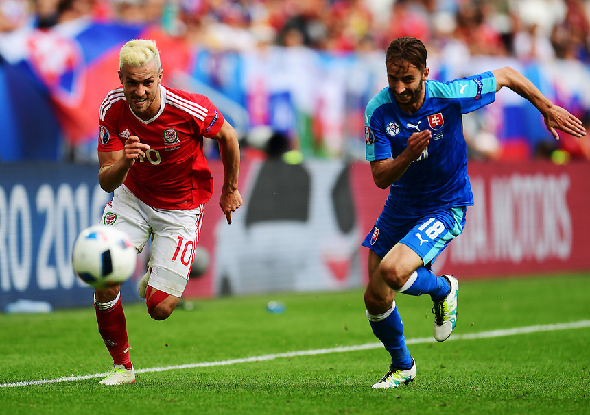 Wales's Aaron Ramsey gives chase to the ball, under pressure from Slovakia's Dusan Svento<br /> <br /> Photographer Kevin Barnes/CameraSport<br /> <br /> International Football - 2016 UEFA European Championship - Group B - Wales v Slovakia - Saturday 11th June 2016 - Nouveau Stade de Bordeaux, Bordeaux<br /> <br /> World Copyright &copy; 2016 CameraSport. All rights reserved. 43 Linden Ave. Countesthorpe. Leicester. England. LE8 5PG - Tel: +44 (0) 116 277 4147 - admin@camerasport.com - www.camerasport.com