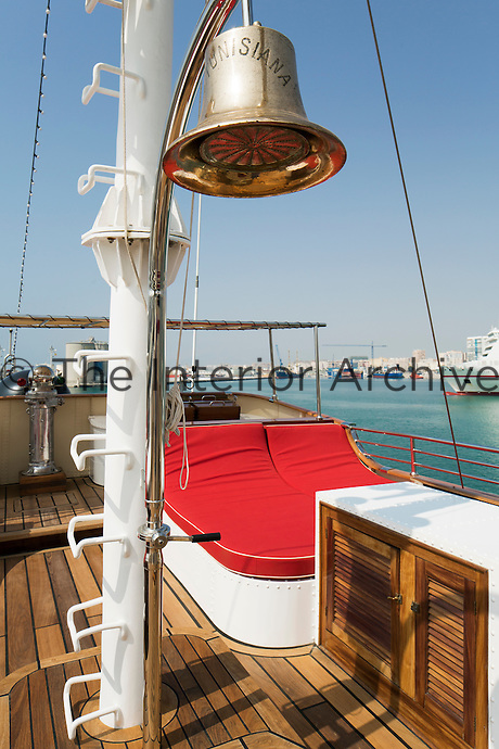 An original ship's bell stands sentinel over a double lounger on one of the sun decks