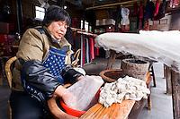 Una donna durante la lavorazione del bozzolo del baco da seta.<br /> Wuzhen &egrave; una piccola citt&agrave; della provincia dello Zhejiang chiamata anche la Venezia d'Oriente per la caratteristica dei canali che corrono lungo i vicoli dell'antica citt&agrave;. E' anche riconosciuta come uno dei centri pi&ugrave; importanti per la produzione e la lavorazione della seta nell'antichit&agrave;. Ancora sono presenti alcune piccole ditte che continuano a lavorare la seta con gli stessi metodi di come si faceva da secoli. Nonostante sia diventata una meta turistica ancora si pu&ograve; respirare la vecchia Cina nel modo di vivere dei cittadini e nel percorrere i vecchi vicoli costruiti con la pietra e rimasti intatti nei secoli.
