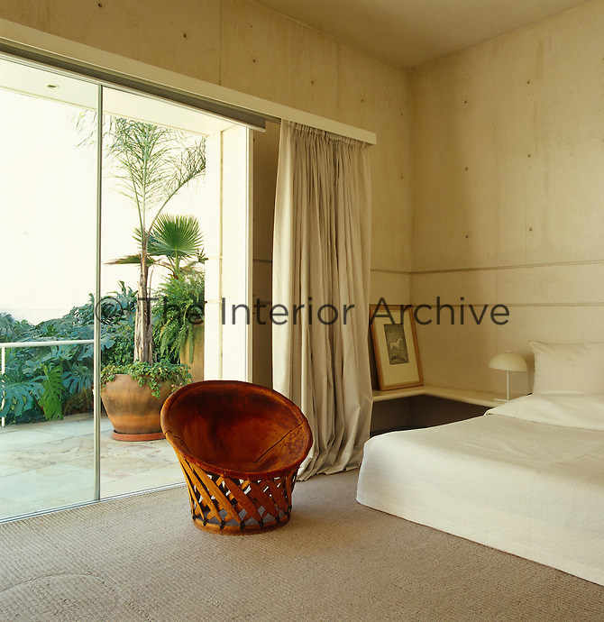 A tub chair sits beside a tall open balcony door in this contemporary Mexican bedroom.