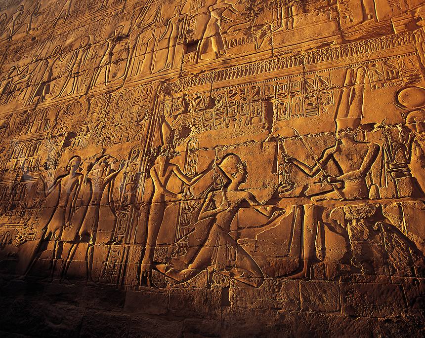 Elaborate carved stone relief with close-ups of pharonic figures in strong evening side-light, at Karnak temple, Luxor, Egyp