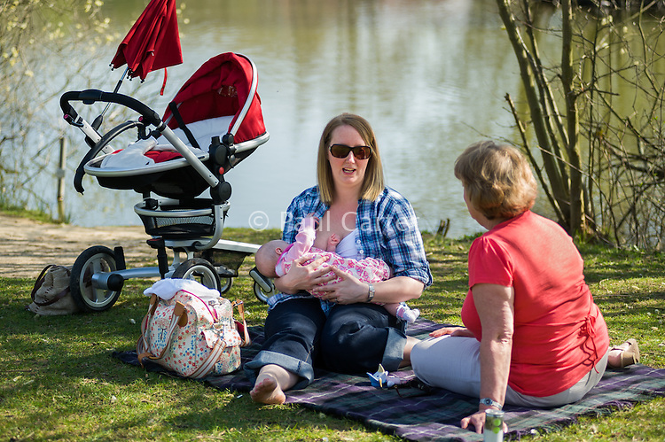A young woman breastfeeding her baby on a picnic whilst talking with her mother in a country park in early spring.<br /> <br /> 27/03/12<br /> Lakeside Park, Eastleigh, Hampshire, UK