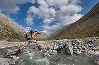 Creek jumping along a tributary that flows into the Marsh Fork of the Canning river in the Arctic National Wildlife Refuge in the Brooks range mountains, Alaska.