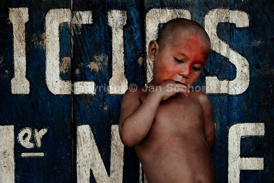 A Nukak Maku boy, having his face painted with the red dye, stands in front of the sanitary house in a refugee camp close to San Jose del Guaviare, Colombia, 4 September 2009.