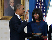 United States President Barack Obama (L) takes the oath of office from U.S. Supreme Court Chief Justice John Roberts as first lady Michelle Obama holds the bible in the Blue Room of the White House in Washington, January 20, 2013.  .Credit: Larry Downing / Pool via CNP