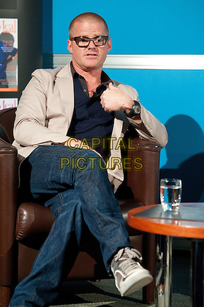 Heston Blumenthal.The Future of Food Q&A.  Experimental British chef and owner of the Fat Duck discusses the future of food, London Media Centre, London, England..August 10th, 2012.full length sitting jeans denim legs crossed beige suit jacket blue top glasses   .CAP/BF.©Bob Fidgeon/Capital Pictures.