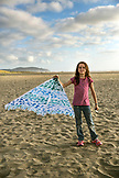 USA, Washington State, Long Beach Peninsula, International Kite Festival, portrait of Lorel Kirby holding her kite at the beach at the end of the day
