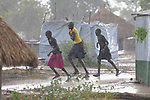 Girls run in the rain in the Rhino Refugee Camp in northern Uganda. As of April 2017, the camp held almost 87,000 refugees from South Sudan, and more people were arriving daily. About 1.8 million people have fled South Sudan since civil war broke out there at the end of 2013. About 900,000 have sought refuge in Uganda.