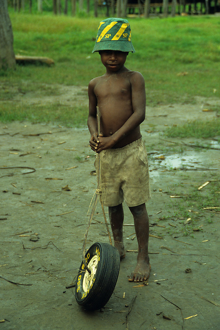 PAPUA NEW GUINEA, SEPIK RIVER, BOY PLAYING WITH TIRE