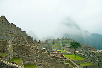 The labyrinth of ruins at Machu Picchu was again shrouded in fog. The famous towering emerald spire of Huayna Picchu was barely visible though the windows and doorways of the greatest archaeological discovery of modern times. By mid-morning the day-trippers began to arrive and the clouds slowly lifted, revealing the valley bellow.