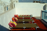A row of sun-loungers, reminiscent of military camp beds, on Moroccan rugs make a comfortable relaxation area on the roof terrace