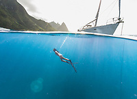A woman free dives off an anchored sailboat on the Na Pali Coast of Kaua'i.