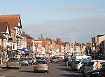 Traffic and people shopping on historic High Street of Marlborough, Wiltshire, England, UK