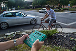 A traffic engineer uses a handheld computer to survey traffic patterns at an intersection near a college where street closing are proposed.
