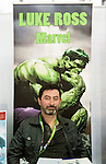 Manhattan, New York City, New York, USA. October 10, 2015. Artist LUKE ROSS sits in front of banner with his drawing of the Hulk variant cover from Marvel comics, at the Artist Alley of the 10th Annual New York Comic Con. NYCC 2015 is expected to be the biggest one ever, with over 160,000 attending during the 4 day ReedPOP event, from October 8 through Oct 11, at Javits Center in Manhattan