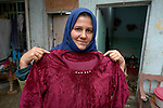 Ekhlas Mohamad holds a dress she made after participating in a sewing course conducted by RNVDO in Mosul, Iraq, which has helped her to earn income for her family. The class was supported by the ACT Alliance.