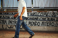Italy. Lazio region. Monterotondo. Dorel Andries is a romanian citizen and has lived in Italy for the last 10 years.  Romanian immigration. He walks by some graffiti which say: Immigration and Rom Welcome (up). There 's no bankers who steal (center). Between your own country and the entire world (down). The Romani, who are known collectively in the Romani language as Romane or Rromane (depending on the dialect concerned) and also as Romany, Romanies, Romanis, Roma, Romsor or Rroms, are an ethnic group living mostly in Europe. Monterotondo is a town and comune in the province of Rome. 2.10.2011 © 2011 Didier Ruef