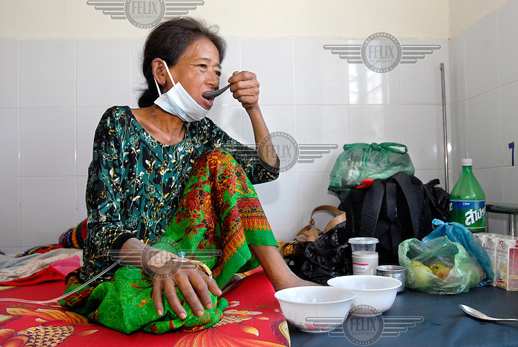 A patient on the ward for people with HIV and tuberculosis (TB) infection in Takeo hospital eats a meal.