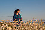 Young woman standing in tall grass sunset portait