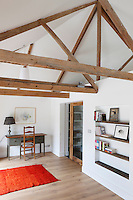 A contemporary rusticity adds to the decoration of this upstairs bedroom in which A-frame beams have been made a feature