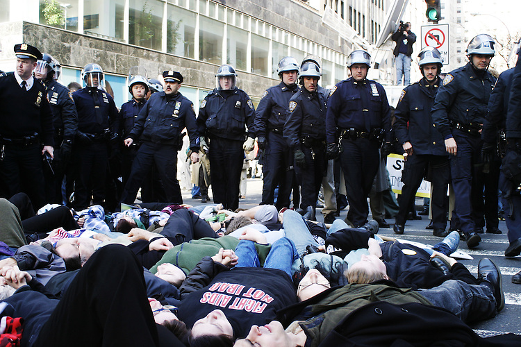 "Hundreds gather at Rockefeller Center in New York City on March 18, 2003 for a ""die-in"" to protest the invasion of Iraq.  At a chosen time all protesters promptly laid down in the middle of 5th Avenue and were arrested en masse.  The demonstration was organized by the M27 Coalition, beginning a day of multiple direct actions against the war throughout the city.  The M27 Coalition, a loose grouping of activist organizations, chose the locale because if its proximity to various media and corporate offices it professed were profiting, either directly or indirectly, from the war."